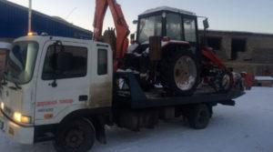 Эвакуатор с прямой платформой везет трактор